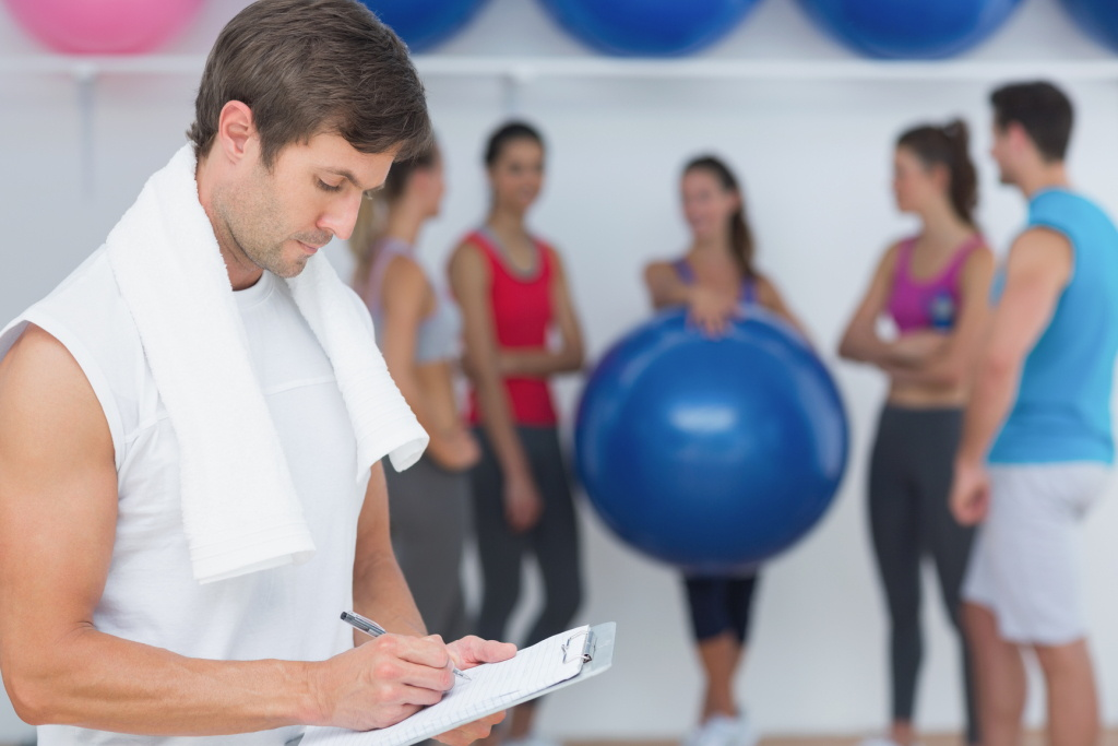 Male trainer writing in clipboard with fitness class in background at the gym