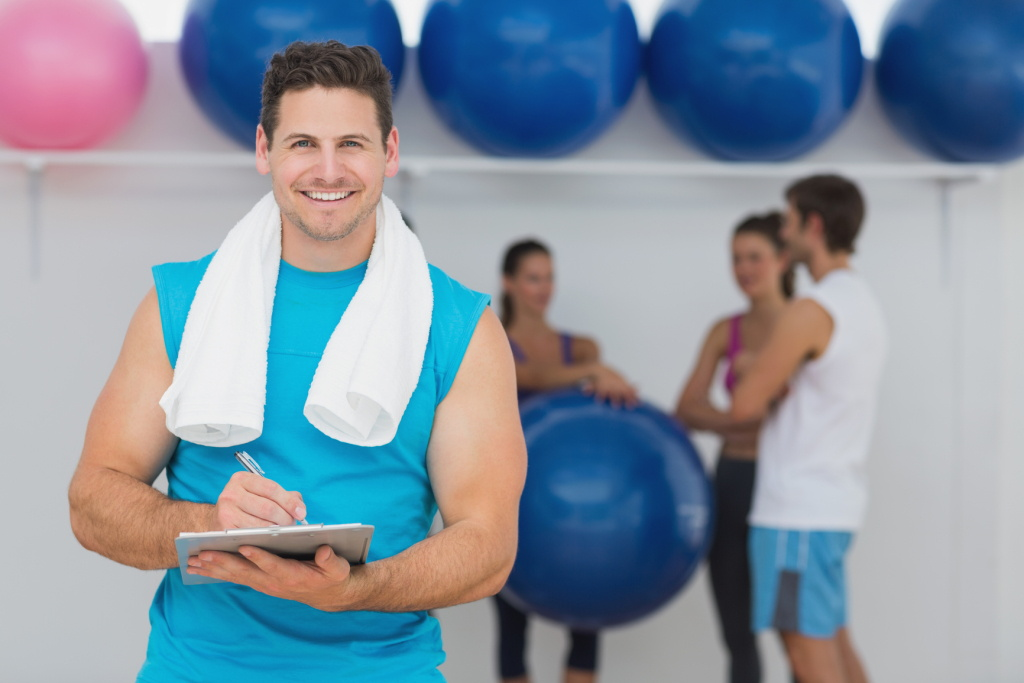 Portrait of a male trainer holding clipboard with fitness class in background at the gym